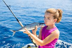 kid girl fishing tuna bonito sarda kissing fish for release - stock photo