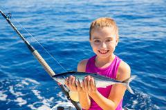 kid girl fishing tuna bonito sarda fish happy with catch - stock photo