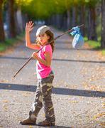 little kid with hobo stick bag and bundle girl saying goodbye - stock photo