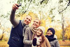 Happy family with camera in autumn park Stock Photos