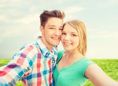 smiling couple with smartphone in suburbs - stock photo