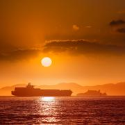 Alcatraz island penitentiary at sunset and merchant ship - stock photo