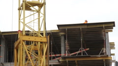 Construction. Man walks on the top of building. Crane. Stock Footage