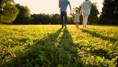 Happy family with two little children walking on meadow. Silhouettes sunset. - stock footage