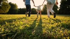 Happy family with two little children running on meadow. Silhouettes sunset. Stock Footage