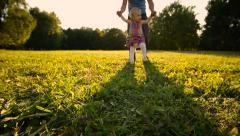 Father and baby walking on meadow. Silhouettes sunset. Low angle shot. - stock footage