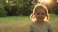 Portrait Adorable Little Girl Smiles outdoor at sunset - stock footage