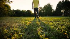 Young man goes through the park in direction from camera. Extreme low angle shot Stock Footage