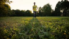 Young man goes through the park toward camera. Extreme low angle shot. Stock Footage