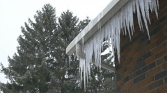 Slow motion snow falling. Icicles hanging from house. Stock Footage