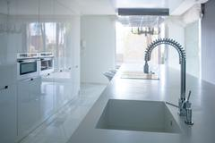 Modern white kitchen perspective with integrated bench Stock Photos