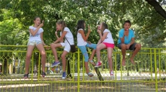 Young boy and girls eating ice cream on fence in the park, kids licking lollipop Stock Footage