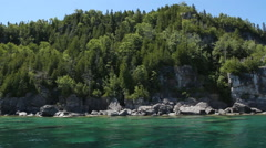 Passing the cliffs and trees of Flowerpot Island in Tobermory, Ontario, Canada. - stock footage