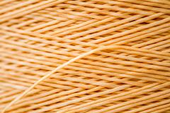 Close up of a Spool of Synthetic Orange Thread - stock photo