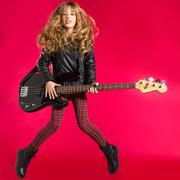 Blond Rock and roll girl with bass guitar jump on red - stock photo