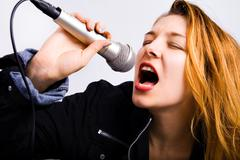 Female rock singer with microphone in hand - stock photo