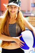 Summer leisure - active happy woman holding a ball - stock photo