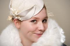 Redhead smiling cheekily in white felt hat and fur Stock Photos
