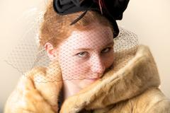 Redhead smiling shyly in black veiled hat and fur coat Stock Photos