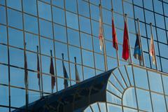 Five flags and their reflections in building - stock photo
