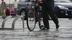 Man Carries A Child In Bicycle Helmet On The Trunk Of The Bike Under The Rain Stock Footage