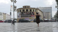 Woman Walks On The Wet Sidewalk Tiles In The Rain Passenger Cars Buildings Lamp Stock Footage