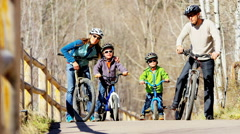 young Caucasian parents sons cycling outdoor recreation active teamwork park - stock footage