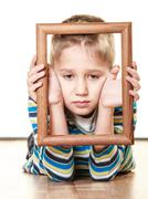 Stock Photo of Little sad boy child framing his face