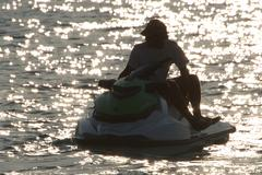 Jet Ski driver silhouetted against backlit waves Stock Photos