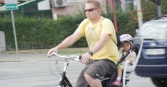 Man In Yellow T-Shirt And Sunglasses Rides On The Bike With Little Kid He Stops Stock Footage