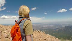 4K pan up a hiker overlooking from the summit of Pikes Peak Stock Footage