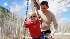 Caucasian family park father child boy healthy outdoor lifestyle playing swing Stock Footage