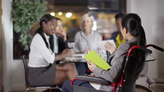 4k Female business group including woman in wheelchair discuss ideas in meeting Stock Footage
