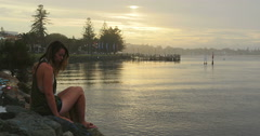 Young woman sits alone on a rock side overlooking the ocean Stock Footage