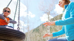 Caucasian family park mother child boy healthy outdoor lifestyle playing swing Stock Footage