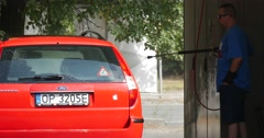 Man In Sunglasses Washes His Red Ford Mondeo Hatchback At The Carwash with a Stock Footage
