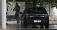 Man At The Carwash Washes His Dark Green Opel Hatchback On The Background Stock Footage