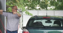 Man In Glasses Uses Brush And Clean His Green Opel Hatchback At The Carwash He Stock Footage