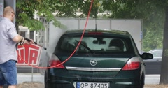 Man In Glasses At The Carwash Carefully Washes His Green Opel Hatchback On Stock Footage