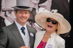 Couple at Royal Ascot laughing at camera - stock photo