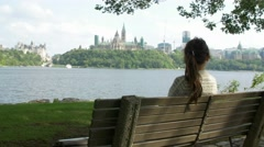 woman voter sits on bench looking towards parliament of Canada - stock footage