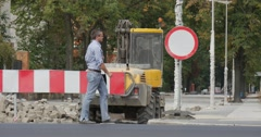 Man Walks Fast On Paved Road In Front of Red-White Roadblock Bulldozer Stands Stock Footage