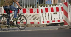 Man On The Bicycle Rides In Front Of Red-White Roadblock Safety Fence Cars Go Stock Footage