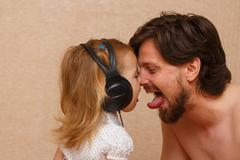 Little girl and dad listens to music. Stock Photos