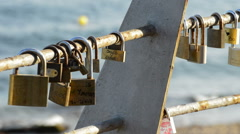 Padlocks with Names of Couples in Love at Sunset with Sea in the Background Stock Footage
