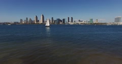 Aerial. Flying  over water in San Diego with Downtown on a background . Yaht. Stock Footage