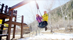 Stock Video Footage of outdoor lifestyle active Caucasian boy girl children happy playing swing tourism