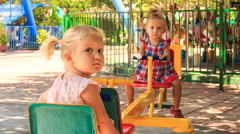 Two little girls rock on swing on play ground in tropical park Stock Footage