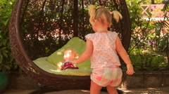 Little blonde girl with hairtails rocks doll on round swing Stock Footage