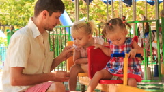 Father feeds little girls on double swing in tropical park Stock Footage